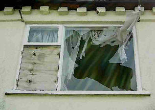 Derelict hopuse, broken window and curtains flapping.