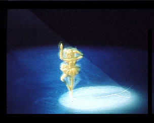 A plastic figure spinning on ice with a spotlight on it