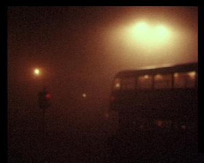 A bus in thick fog at red traffic lights