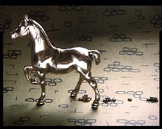 A brass model horse with brass nuts trailing behind as its droppings.