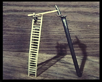 Nail with a tiny ladder and model of a man with tiny hammer