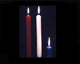 Three red white and blue candles, the blue one burnt down.